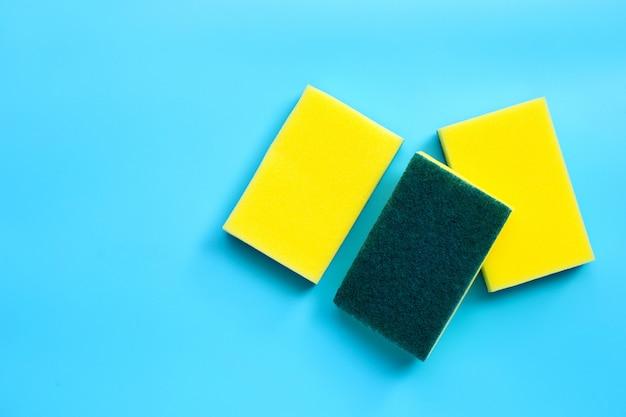 Esfregue as esponjas sobre fundo azul. copie o espaço