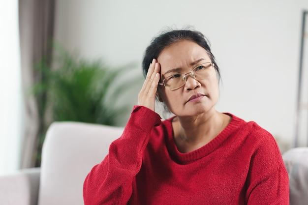 Esgotado, cansado, deprimido, estressado, pensativo, maduro, mulher sênior, sofrendo de dores de cabeça, doenças cerebrais, problemas mentais, conceito de alzheimer.