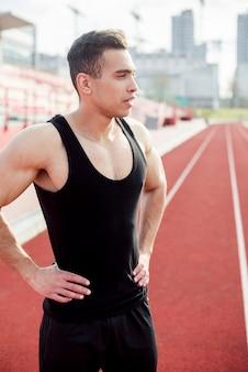Esgotado jovem atleta do sexo masculino em pé na pista de corrida