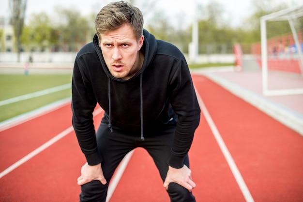Esgotado jovem atleta masculino em pé na pista de corrida, olhando seriamente