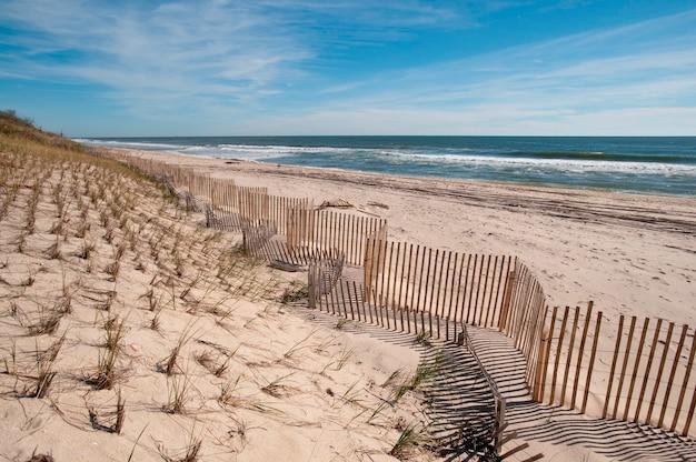Esgrima ao longo da praia nos hamptons