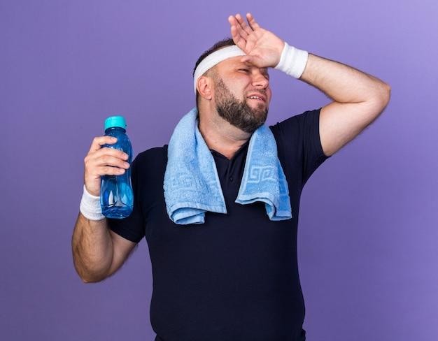 Eslavo adulto e desportivo com uma toalha em volta do pescoço, usando uma faixa na cabeça e pulseiras segurando uma garrafa de água e colocando a mão na testa isolada na parede roxa com espaço de cópia