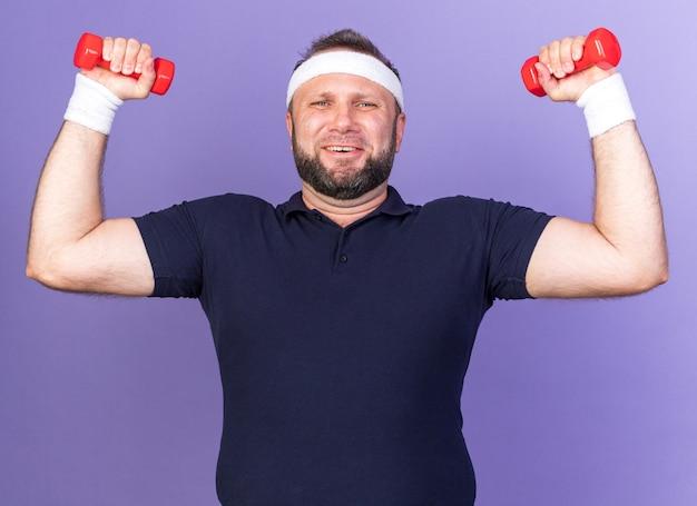 Eslavo adulto e esportivo sorridente usando bandana e pulseiras segurando halteres isolados na parede roxa com espaço de cópia