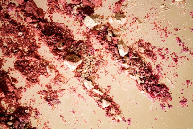 Esmagado cosméticos mineral orgânico sombra blush e pó cosmético isolado em fundo dourado.