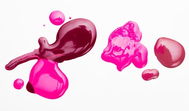 Esmalte colorido brilhante derramado com pano de fundo branco