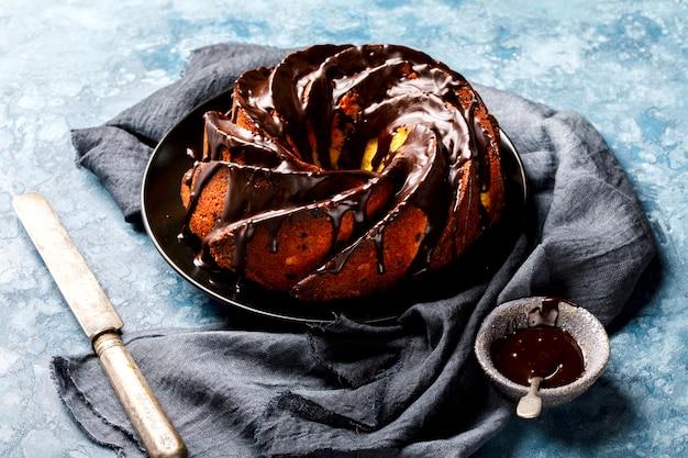 Esmalte do chocolate do bolo em um fundo azul.