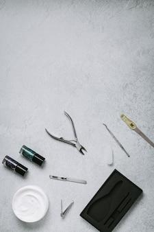 Esmalte para unhas, ferramentas de manicure e creme para as mãos na superfície plana da mesa de concreto cinza. como fazer manicure no conceito de casa. faça as unhas sozinha enquanto fica em casa durante a quarentena, vista de cima