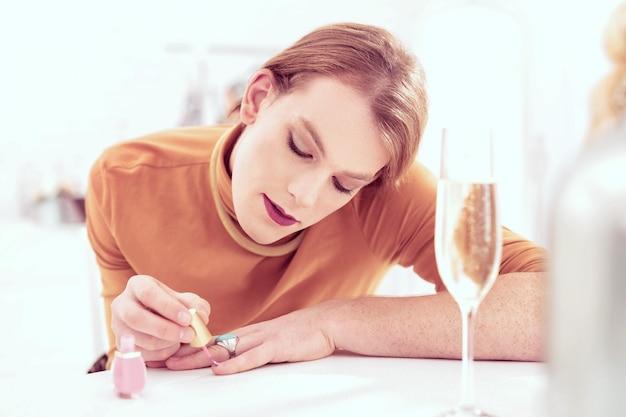 Esmalte rosa bebê. agradável homem trans ruivo de pêlo curto cobrindo cuidadosamente as unhas com uma cor feminina