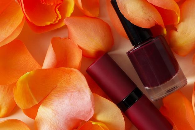 Esmalte vermelho escuro e recipientes de batom em pétalas de rosa close-up