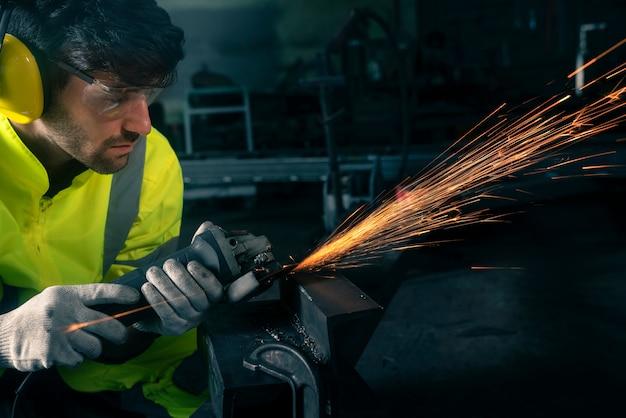 Esmerilhamento de roda elétrica em estrutura de aço na fábrica, esta imagem pode ser usada para conceito industrial, trabalhador e de segurança