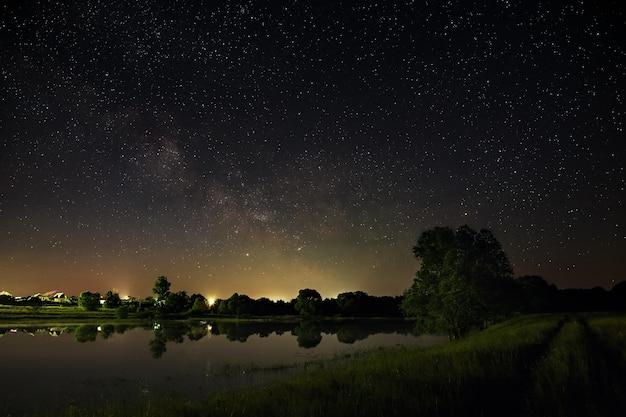 Espaço com estrelas no céu noturno. a paisagem com o rio e as árvores é fotografada em longa exposição.