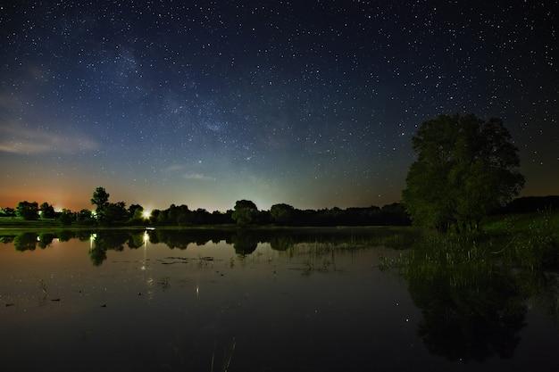 Espaço com estrelas no céu noturno a paisagem com o rio e as árvores em uma longa exposição