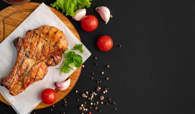 Espaço de cópia de carne grelhada, superfície escura, ervas, alface, tomate, tempero preto nas colheres de madeira