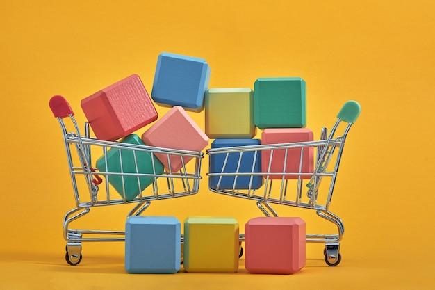 Espaço de cópia de estilo de maquete de cubos de madeira vazios com carrinhos de compras em fundo amarelo. modelo de blocos coloridos para local de design criativo para texto