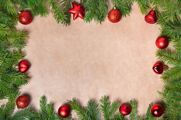 Espaço de cópia plana leigos de natal. brinquedos de natal vermelhos e raminhos de abeto em um fundo marrom.