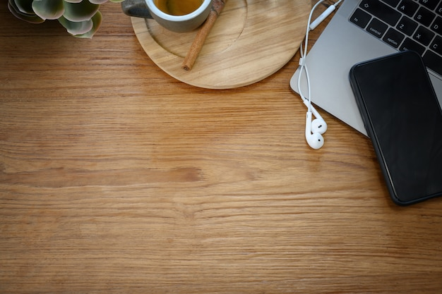 Espaço de madeira da vista superior com portátil, café, planta da casa e espaço da cópia.