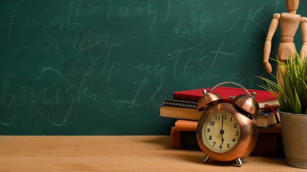 Espaço de maquete na mesa de madeira com despertador vintage, figura de madeira, livros e planta sobre fundo verde lousa. volta às aulas, mesa de estudo