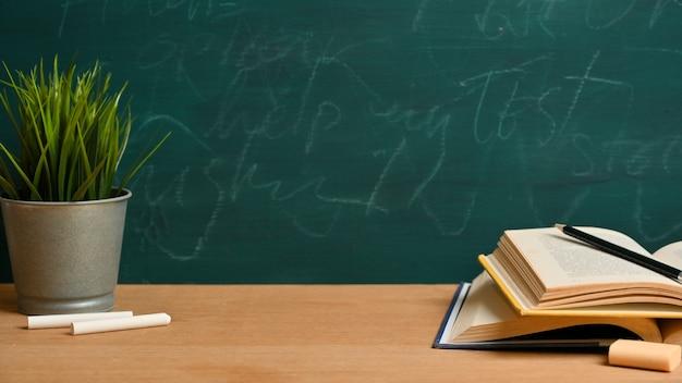 Espaço de maquete na mesa de madeira com livros abertos, lápis, giz, planta sobre lousa verde. sala de aula ou conceito de escola