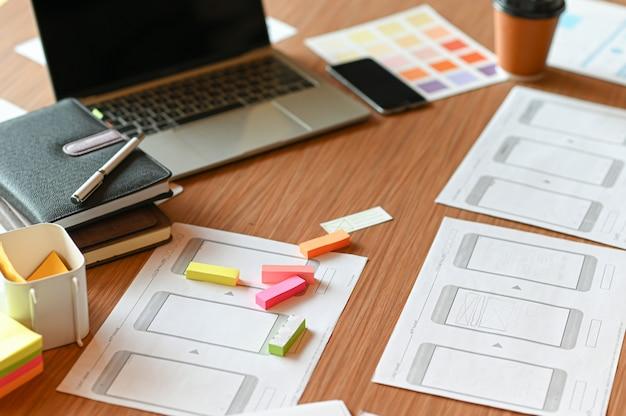 Espaço de mesa de design para designers. cartas de cores, telefones modelo e tablet.