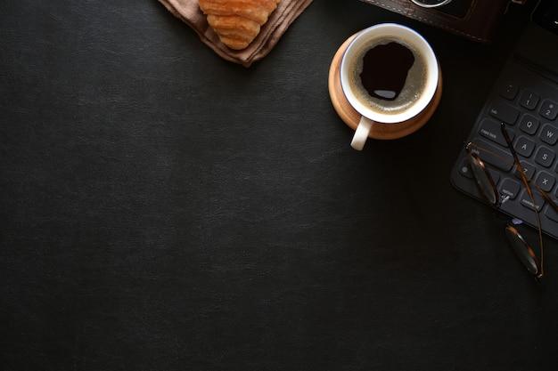 Espaço de mesa de escritório em casa com café, croissant e espaço de cópia