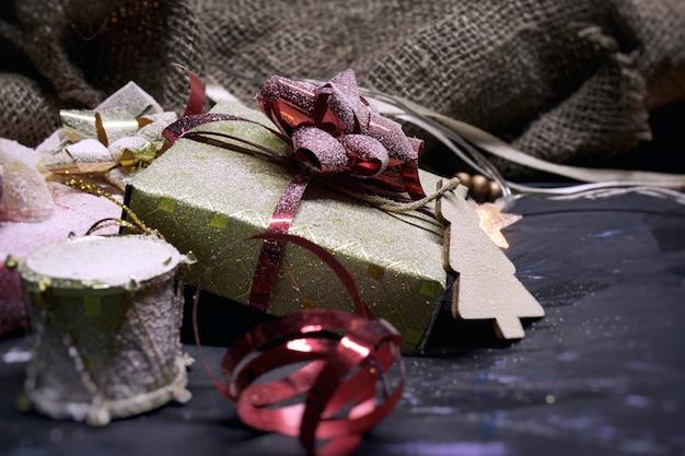 Espaço de natal e ano novo. presentes em uma caixa com decoração com fitas e laços com serapilheira em um espaço escuro.