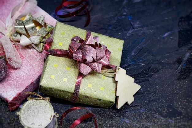 Espaço de natal e ano novo. presentes em uma caixa com decoração com fitas e laços em um espaço escuro.