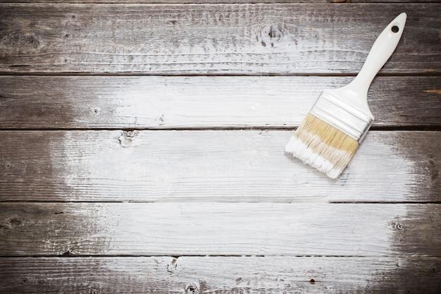Espaço de tinta branca com pincel sobre fundo madeira