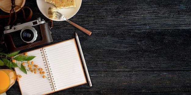 Espaço de trabalho aconchegante com caderno em branco com torradas de pão e um copo de suco de laranja na superfície da mesa de madeira preta