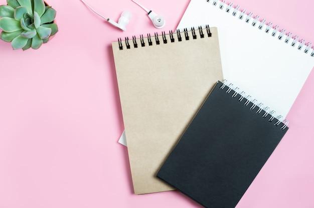 Espaço de trabalho: blocos de notas, fones de ouvido e flor suculenta no fundo rosa.