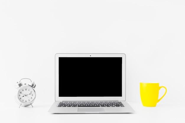 Espaço de trabalho branco com laptop e caneca amarela