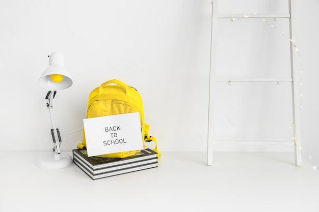 Espaço de trabalho branco para aluno com mochila amarela