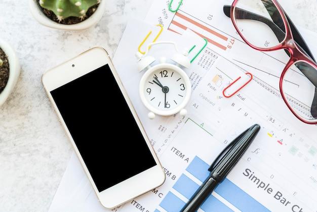 Espaço de trabalho com artigos de papelaria e documentos com smartphone