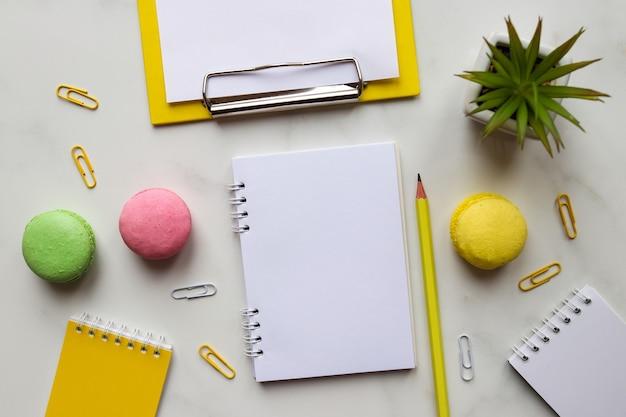 Espaço de trabalho com blocos de notas, lápis, planta e macaroons em mármore