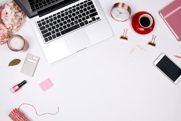 Espaço de trabalho com buquê floral rosa, smartphone, notebook em fundo branco.