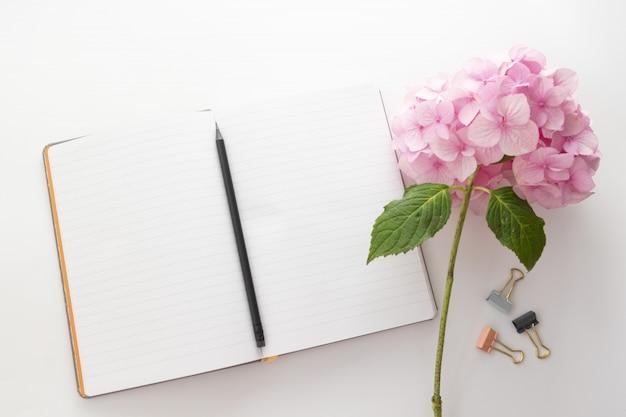 Espaço de trabalho com caderno aberto, lápis e flor rosa de hortênsia.