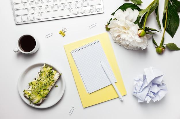 Espaço de trabalho com caderno em branco, teclado, material de escritório