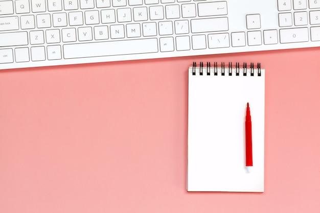 Espaço de trabalho com caderno espiral em branco com teclado em coral