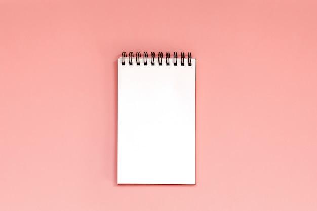 Espaço de trabalho com caderno espiral em branco no coral