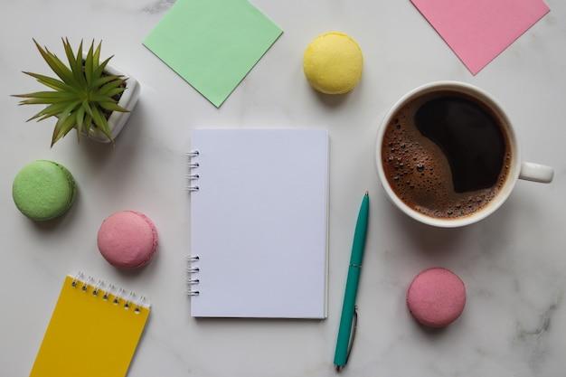 Espaço de trabalho com cadernos, lápis, caneta, planta, xícara de café e biscoitos em mármore