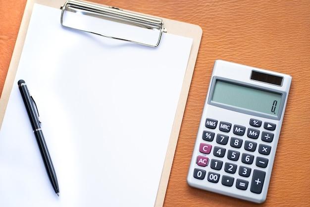 Espaço de trabalho com calculadora, caneta, laptop, área de transferência vazia em fundo de couro.