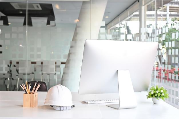 Espaço de trabalho com computador, capacete de segurança e lápis na mesa de escritório.