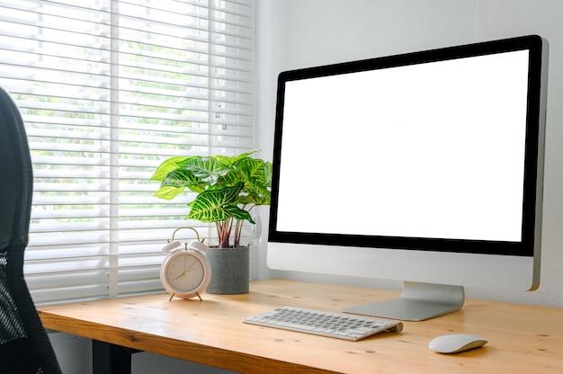 Espaço de trabalho com computador com tela em branco e material de escritório