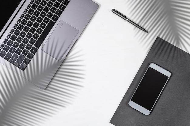 Espaço de trabalho com computador moderno, telefone celular e caneta com sombras de folhas de palmeira