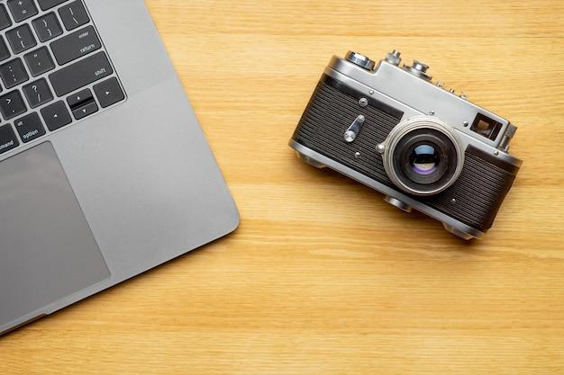 Espaço de trabalho com computador portátil e câmera na mesa de madeira. vista do topo