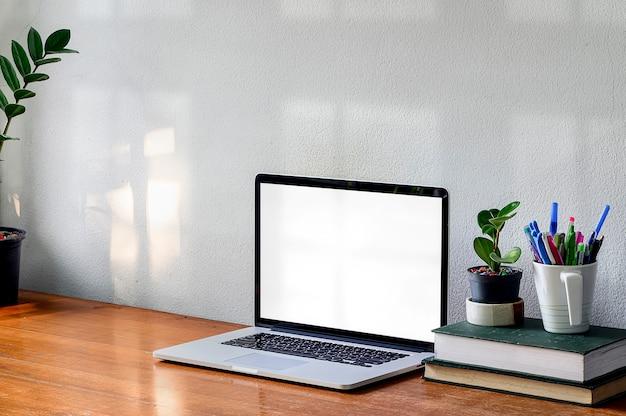 Espaço de trabalho com computador portátil, livro e planta de casa no muro de concreto branco de mesa de madeira.