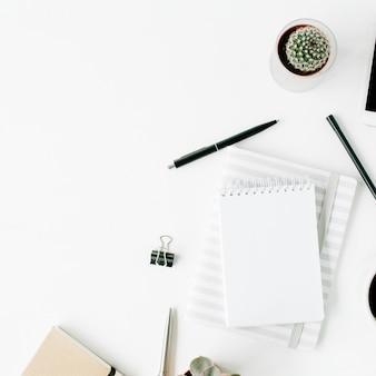 Espaço de trabalho com diário em branco, fones de ouvido, café, suculenta e relógio em branco.