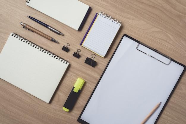 Espaço de trabalho com diário ou caderno e caneta, lápis, hightlight caneta, clipe de metal na madeira