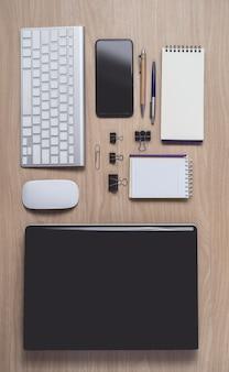 Espaço de trabalho com diário ou caderno e prancheta, laptop, mouse, teclado, telefone inteligente, lápis, caneta