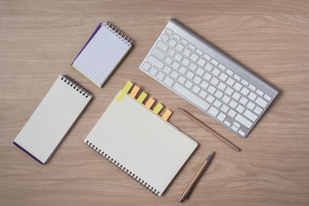 Espaço de trabalho com diário ou caderno e prancheta, teclado, lápis, notas autoadesivas
