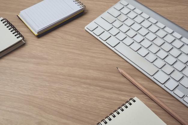 Espaço de trabalho com diário ou caderno e prancheta, teclado, lápis, notas sobre fundo de madeira